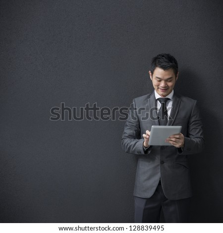 Chinese man with a tablet computer. Asian business man using digital tablet computer, leaning against a black wall. - stock photo