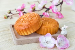Chinese Mid-Autumn festival composition: traditional chinese moon cakes, moon hare and branch with pink flowers are on a light straw mat