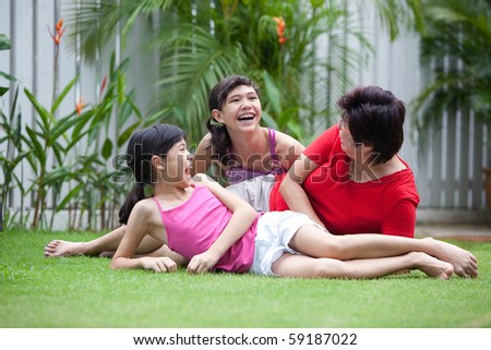 Chinese mom having fun with her daughters in the garden