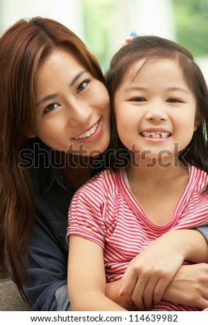 Chinese Mother And Daughter Sitting On Sofa At Home Together
