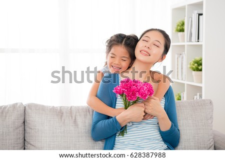 chinese mother sitting on the sofa in the living room little daughter giving her hug from behind and sent to mother's day carnations bouquets and happy together celebrate festival with copyspace. #628387988