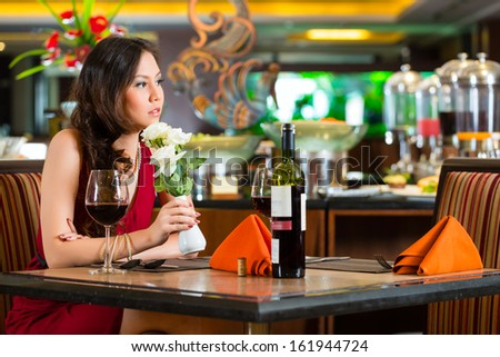 Chinese nervous, hoping, lonely, dreamy, heartsick woman in a restaurant waiting for a date got stood up  Stock photo ©