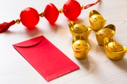 Chinese New Year and Lunar New Year celebrations with gold bar red envelope orange and hot tea. (with the character