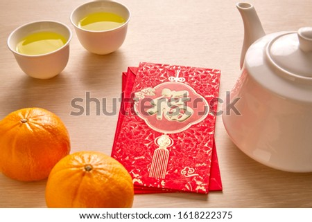 """Chinese New Year and Lunar New Year celebrations with gold bar red envelope orange and hot tea. (with the character """"fu"""" meaning fortune Prosperity and Spring going smooth."""