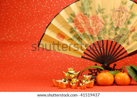Chinese new year decoration--Traditional fan with gold ingot and orange on festive background.