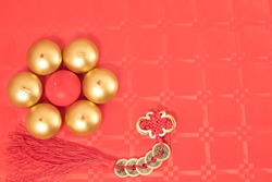 Chinese new year decoration with  two color candles on a red table with red and gold tableclothsand ancient Chinese coins from the Qing period, Translation