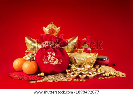 Chinese new year decorations, Gold Coins and money bag with character meaning, 'luck riches healthy' on red background. Stockfoto ©