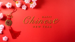 Chinese new year festival decorations made from chinese good luck symbol and plum blossom on a red background.  Flat lay, top view with space.
