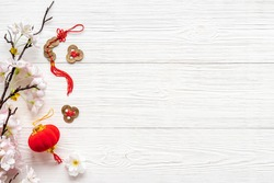 Chinese new year flat lay with lucky knots, red laterns and sakura branch bloom
