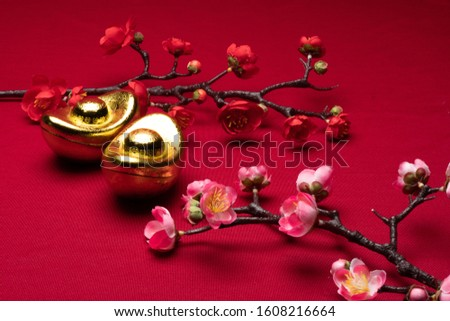 Chinese New Year gold and flowers decorations in red background with assorted festival decorations. Chinese characters in decoration means generous of wealth, prosperity and luck