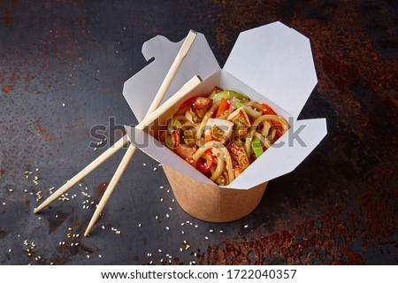 Chinese noodles with chicken and vegetables in a cardboard box on a dark background, Asian food delivery, concept of street food,  copy space ストックフォト ©