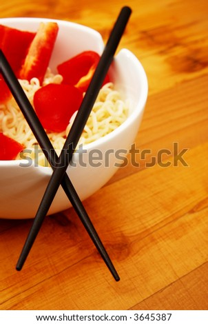 Chinese noodles with chop sticks in a bowl on wooden counter with some peppers in the noodles
