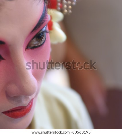 chinese opera actress is painting her face backstage