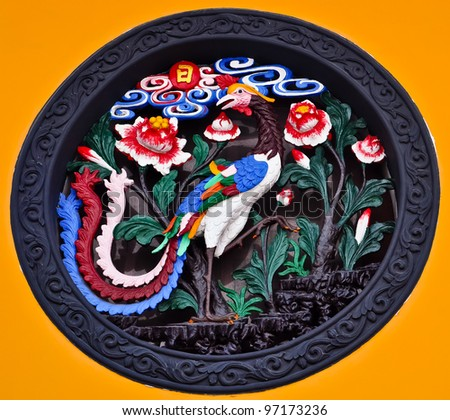 chinese ornament depicting a colorful peacock and flowers