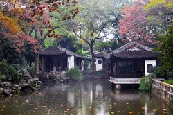 Chinese pagodas on a lake in a historic garden called Qiuxiapu. The mood is mystical, fog hangs over the water.
