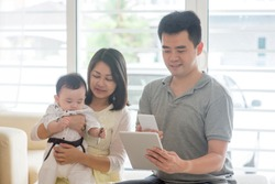 Chinese people scanning QR code with smart phone. Asian family at home, natural living lifestyle indoors.