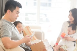 Chinese people scanning QR code with smart phone. Happy Asian family at home, natural living lifestyle indoors.