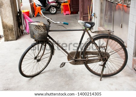 Chinese people stopping classic retro vintage old bicycle with basket at front of house in old town at Chaozhou or Teochew in Guangdong, China