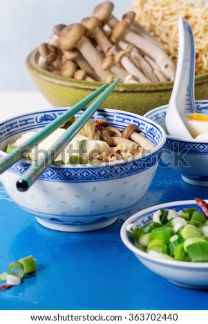 Chinese porcelain bowl of asian ramen soup with feta cheese, noodles, spring onion and mushrooms, served with turquoise chopsticks and nboiled egg over white kitchen table with blue stone board.  - stock photo