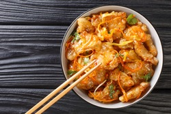 Chinese pork in sweet and sour sauce with carrots, onions, garlic and ginger close-up in a bowl on the table. horizontal top view from above
