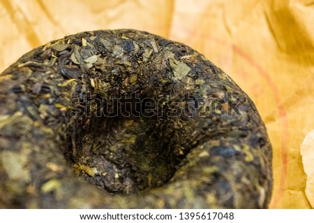 Chinese pressed puer tea on wrapping paper, close-up, macro #1395617048