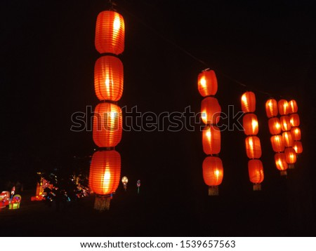 Chinese red lanterns in the park. Retro style lantern at night. Beautiful colorful illuminated lamp in the garden.