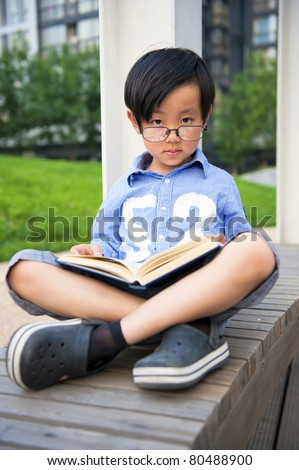 Chinese school boy reading a book