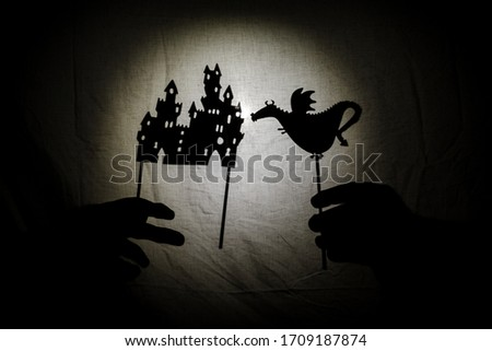 Chinese shadow theater for children projected on a bed sheet, themed of Saint George. The shadows are of cardboard, you can see the hand that manipulates them. dragon, tales, storyteller, castle Foto stock ©