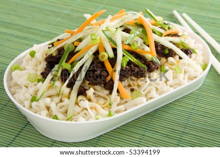 "Chinese spaghetti or ""zha jiang mian"" - noodles topped with fermented soybean paste and garnished with fresh cucumber, carrots, and green onion."