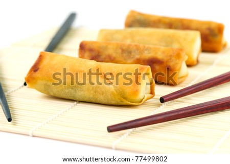 Chinese spring rolls with chosticks on the bamboo mat