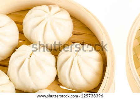 Chinese steamed buns in bamboo steamer basket isolated on white