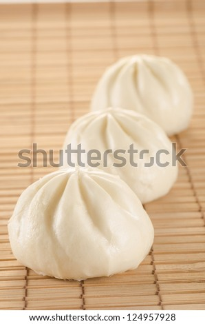 Chinese steamed buns on the bamboo mat background