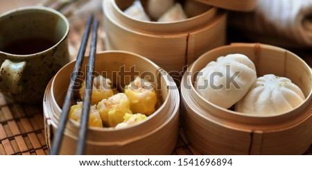 Chinese steamed dumpling and steamed pork bun in a bamboo steamer with chopstick on wooden table  #1541696894