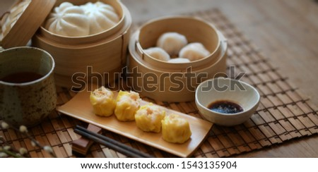 Chinese steamed dumpling and steamed pork bun in a bamboo steamer with chopstick on wooden table  #1543135904