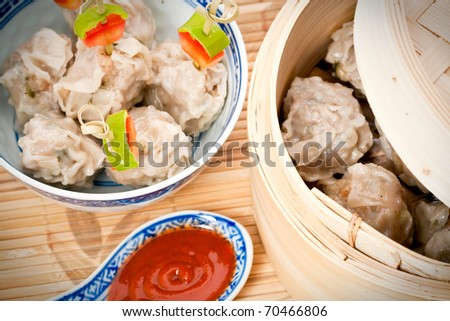 Chinese steamed dumplings served in a traditional bamboo steamer basket, with a Chinese bowl and sauce in a ceramic spoon