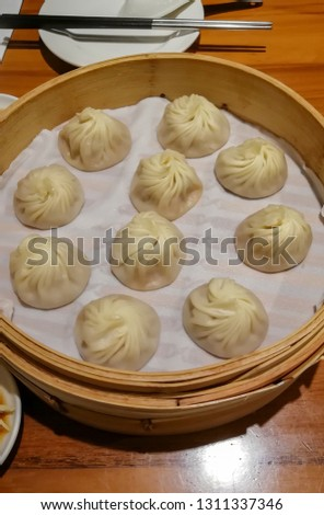 Chinese steamed steamed bun (baozi) named Xiaolongbao also called a soup dumpling. It is traditionally prepared in xiolong small bamboo steaming basket. #1311337346