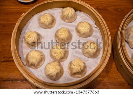 Chinese steamed steamed bun ( baozi ) named Xiaolongbao also called a soup dumpling. It is traditionally prepared in xiolong small bamboo steaming basket. #1347377663