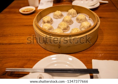 Chinese steamed steamed bun ( baozi ) named Xiaolongbao also called a soup dumpling. It is traditionally prepared in xiolong small bamboo steaming basket. #1347377666