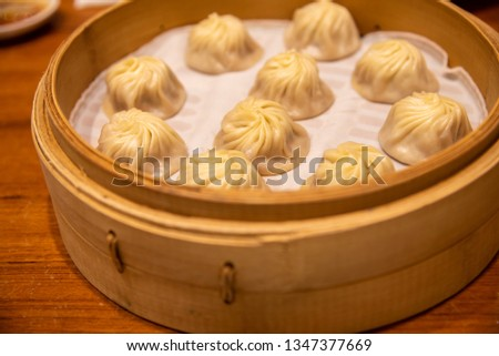 Chinese steamed steamed bun ( baozi ) named Xiaolongbao also called a soup dumpling. It is traditionally prepared in xiolong small bamboo steaming basket. #1347377669