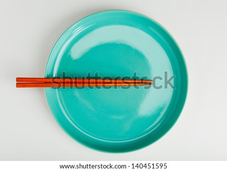 chinese style chopsticks put on green dish top view close up