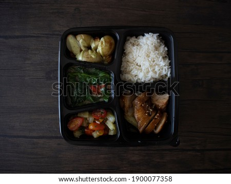 Chinese Style Rice Bento. Chinese Takeaway in a Bento Box. Bento flatlay on wooden table, top down shot.