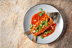 Chinese sweet and sour fish carp squirrel or songshu yu under sweet and sour sauce topped with fresh cilantro served on a plate on a stone background, top view, copy space, close-up