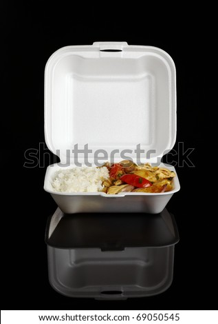 Chinese take-away food: Chicken with tomatoes, green onion, onions and potatoes accompanied by white rice in a styrofoam box photographed on black