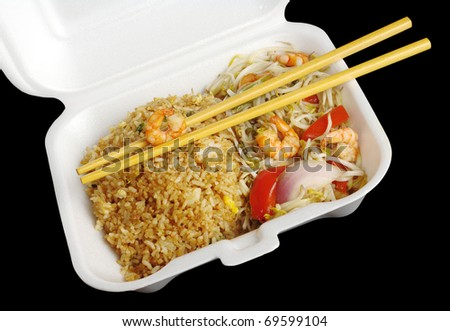 Chinese takeout food: Fried rice with king prawns and vegetables with wooden chopsticks in a styrofoam box photographed from top on black