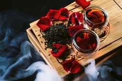 Chinese tea ceremony. Still life with traditional Asian Yunnan black tea, red tea in classic cups and rose petals as symbol of flower flavor of drink