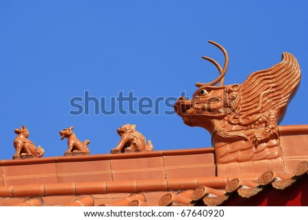 Chinese temple roof with red brown dragon head sculpture on the roof  in Thailand