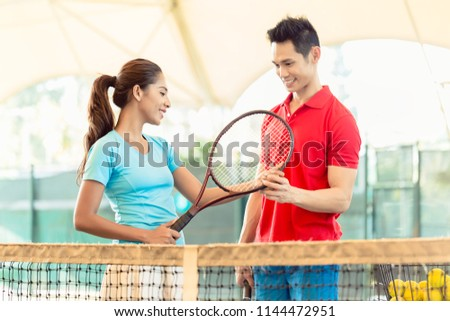 Chinese tennis instructor smiling while teaching a beginner female player the correct grip for holding the racket as a professional player