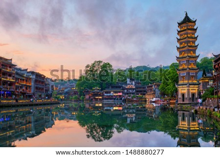 Chinese tourist attraction destination - Feng Huang Ancient Town (Phoenix Ancient Town) on Tuo Jiang River with Wanming Pagoda illuminated at night. Hunan Province, China