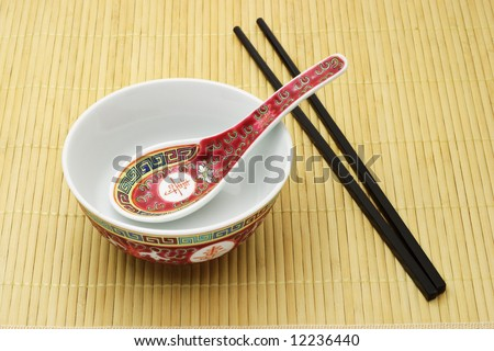 Chinese traditional bowl, spoon and chopsticks arranged on bamboo mat
