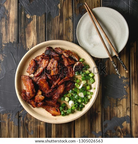 Chinese traditional dish Cantonese BBQ Pork Belly with spring onion served in ceramic plate with chopsticks over dark wooden plank background. Flat lay, space. Asian style dinner. Square image